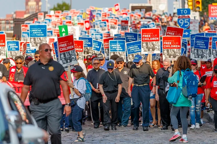 Members of the clergy lead thousands of union protesters from Penn's Landing to the Custom House on Chestnut Street to protest family separations by the administration on August 15, 2018.