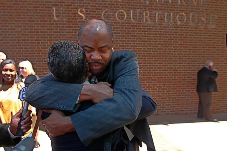 Linwood Norman, center, one of the six Philadelphia Police narcotics officers found not guilty on Thursday, gets a big hug from a family member, after coming down to Market Street after the verdict. (Michael Bryant / Staff Photographer)
