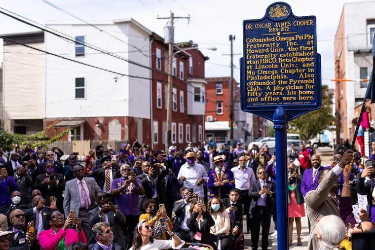A heavily purple crowd claps and cheers as the Pennsylvania historical marker in honor of Dr. Oscar James Cooper was unveiled Saturday in North Philadelphia.