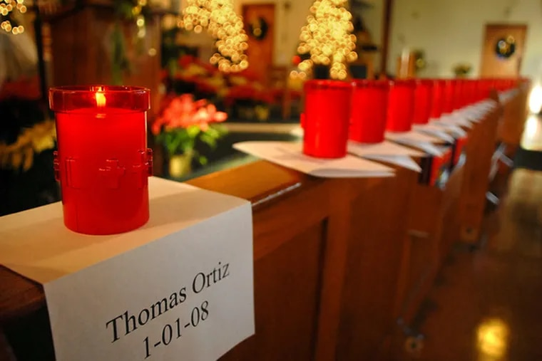 Scores of votive candles, left, were lighted to the memories of the 55 people who died violent deaths in Camden during the year. Their names were inscribed on a ceremonial scroll, right, placed on the altar of St. Joan of Arc Roman Catholic Church.