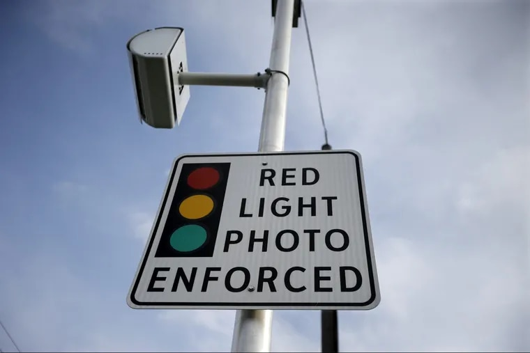 A red light photo enforcement sign is seen below a red light camera Tuesday, Dec. 16, 2014, in Lawrence Township, N.J. It and others across the state went dark when the five-year pilot program ended later that month.