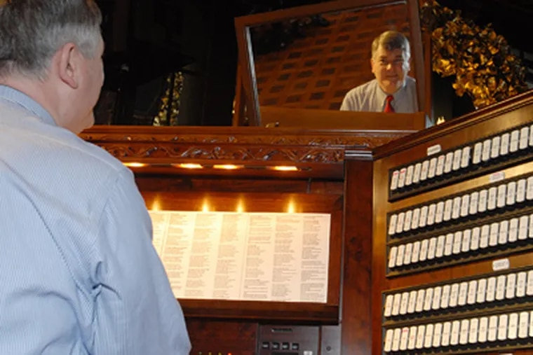 Marc Cheban is reflected in the mirror above the 55-ton pipe organ as he plays for yesterday's caroling session at Longwood. (Bob Williams / For the Inquirer)