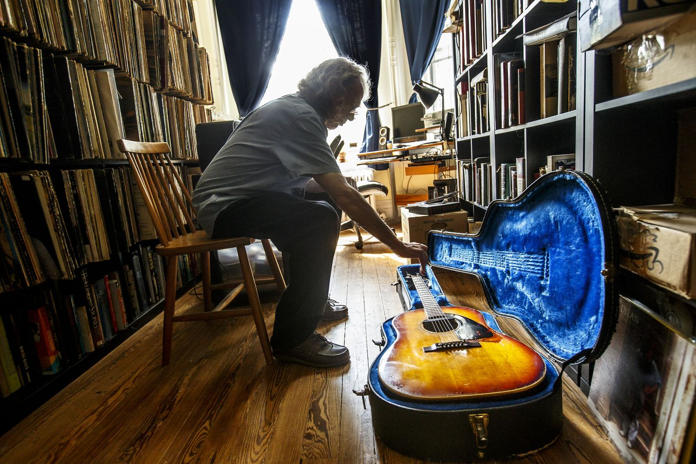 Peter Stone Brown, a mainstay on the Philly music scene, reaches for his 1965 Epiphone Texan guitar at his residence in West Mount Airy.