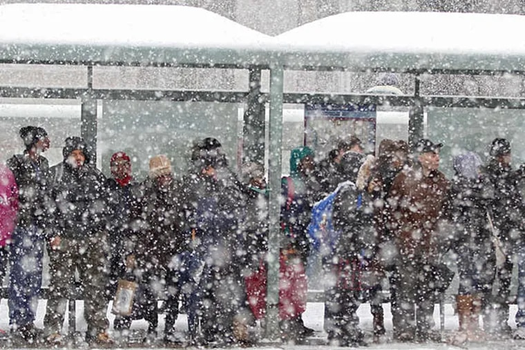 """At a crowded stop, passengers wait for a bus that might already be full and won't stop. The long cold snap has only increased the crowding, and what SEPTA calls """"pass-ups."""" (Michael Bryant/Staff Photographer)"""