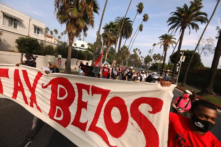 """Amazon worker Derrick Palmer (right) helps carry a banner that states """"Tax Bezos"""" while joining about 100 people who march to Amazon founder Jeff Bezos' mansion to lobby for higher wages, the right to unionize and a series of reforms in the way the giant company handles the COVID-19 crisis, in Beverly Hills last October."""