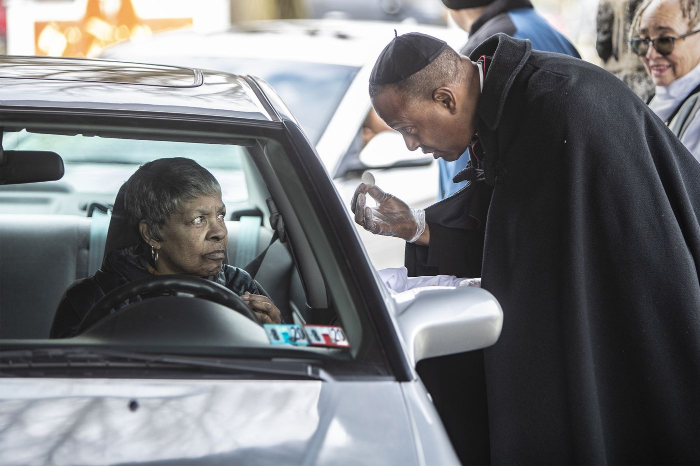 The Rev. Martini Shaw (right) gives a communion wafer to a St. Thomas parishioner as she drives through a covered area of the church in Philadelphia's Overbrook Farms neighborhood.