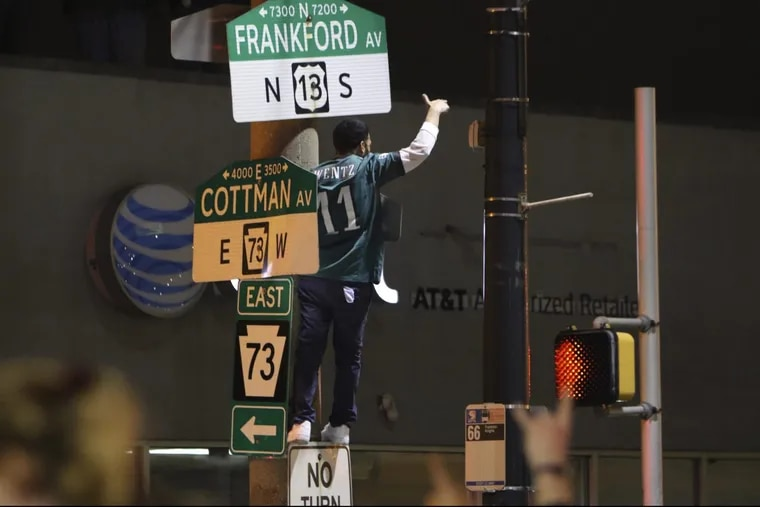 A fan climbs a pole at Cottman and Frankford Avenues in Mayfair following the Eagles' win over the Minnesota Vikings in the NFC championship game.
