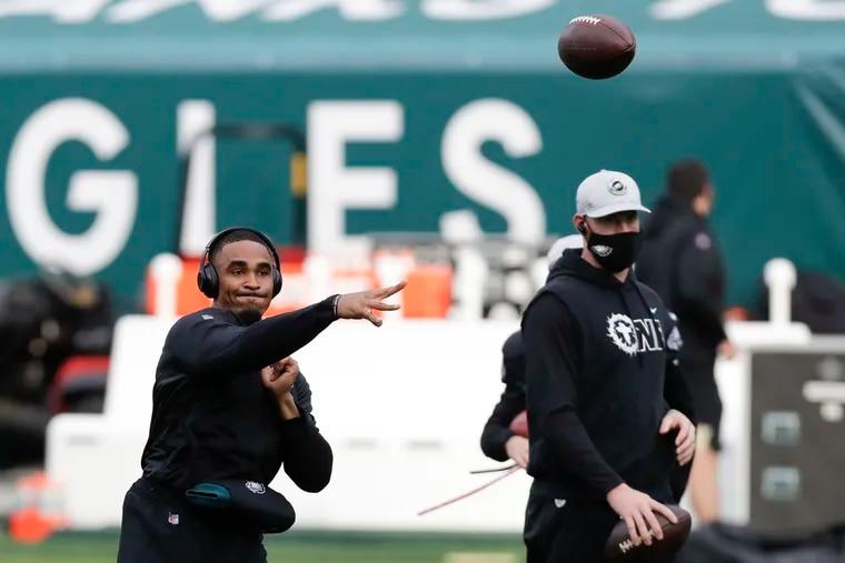 Eagles quarterback Jalen Hurts warms up alongside Carson Wentz before last week's game against the Saints.