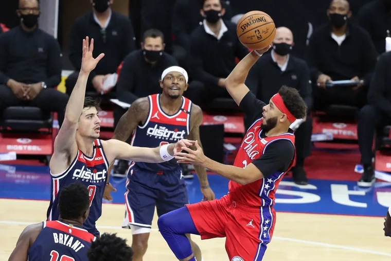 Seth Curry, right, goes up for a basket against Deni Avdija and Bradley Beal during Wednesday's 113-107 victory over the Wizards.
