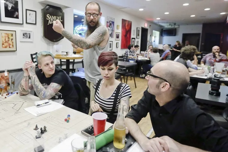 Dungeon master Don Caraco (standing) and seated (from left) Joshua Male, Emma Aprea and Aaron Wolfson play Dungeons and Dragons at the Bllack Cat Tavern on 12th.