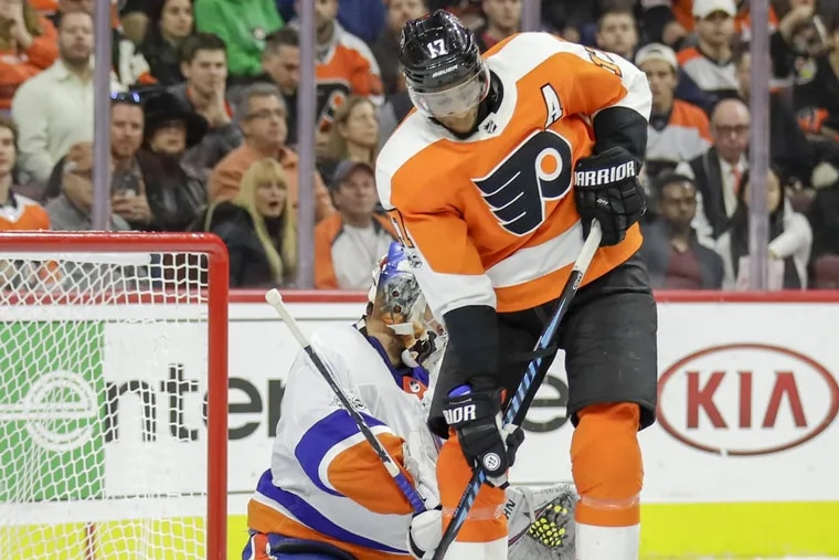 Wayne Simmonds battles in front of Islanders goalie Thomas Greiss during the Flyers' seventh straight loss Friday, a 5-4 overtime defeat. If the Flyers continue to struggle, Simmonds could be put on the trading block.