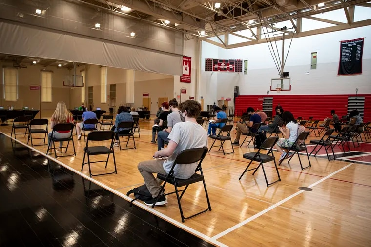 Faculty, staff, and students wait in the observation area after receiving their first COVID-19 vaccination shot at the Haverford College clinic in the athletic center in Haverford on Wednesday, April 13, 2021. Haverford is requiring vaccination for students in the fall semester.