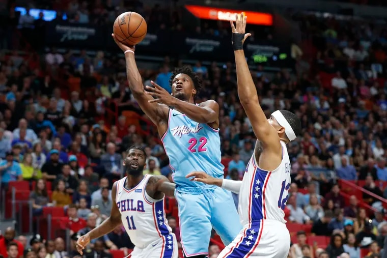 Miami's Jimmy Butler (22), who scored 25 points, goes up for a shot against the 76ers' Tobias Harris (12) and James Ennis III (11) in the first half.