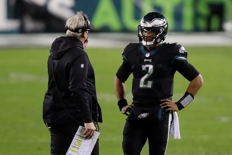 Eagles quarterback Jalen Hurts talks with head coach Doug Pederson during Sunday's win over the New Orleans Saints.