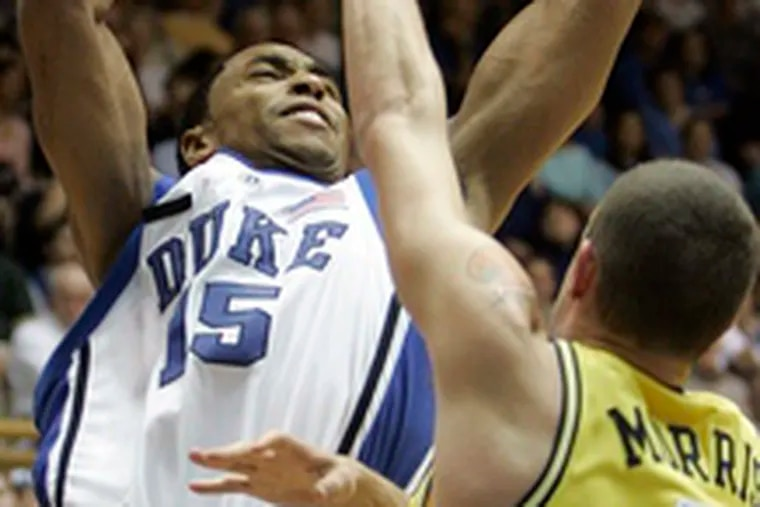 Duke's Gerald Henderson gets off a shot over Michigan's K'Len Morris in a 95-67 victory for the Blue Devils at home.