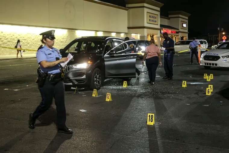 Police officers from the 35th District process the scene outside the ShopRite on East Olney Avenue where a man, 18, was fatally shot and a woman, 19 was injured while sitting inside a BMW SUV in the parking lot on Monday, Aug.16, 2021.