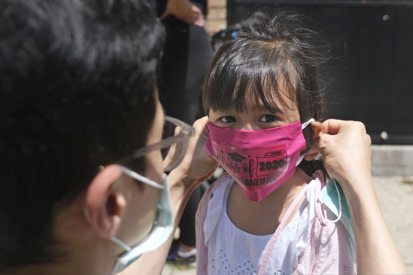 Olivia Chan's father helps her with a new mask she received during a graduation ceremony for her Pre-K class in front of Bradford School in Jersey City.