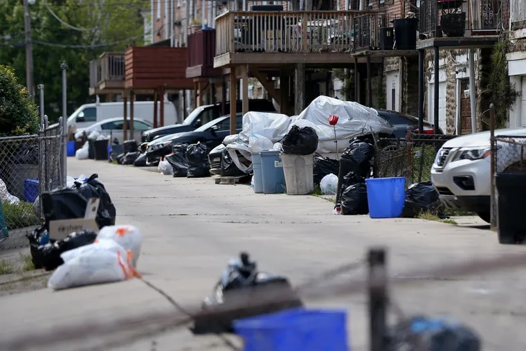 Bags of garbage sit along the street before being picked up in Philadelphia's Ogontz section. Households are generating more trash as people stay home during the coronavirus pandemic.