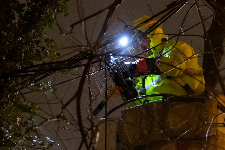 PSE&G troubleshooter Alberto Alfaro works in the pouring rain to restore power to a customer on Church Street in Blackwood, N.J., just before 11 p.m. on Thursday. Storms on Christmas Eve and Christmas morning brought heavy rain and high winds causing flooding, downed trees and power outages to the area.