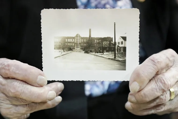 92 year old Longfellow alumna Bette Bailey holds a photo of the school as it looked around 1933 when she attended the Longfellow Elementary School in Pennsauken. The school will be torn down and replaced with a community park by next year. In a final goodbye, alumni of Longfellow Elementary School are touring the aging building one last time.