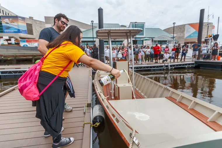 Vuochleng Kim, 15, from Bodine High School, pours sparkling apple cider to christen the JAWN, a boat that she and 70 other high school students built as part of a program at the Independence Seaport Museum that aims to expose underserved populations to science and technology.