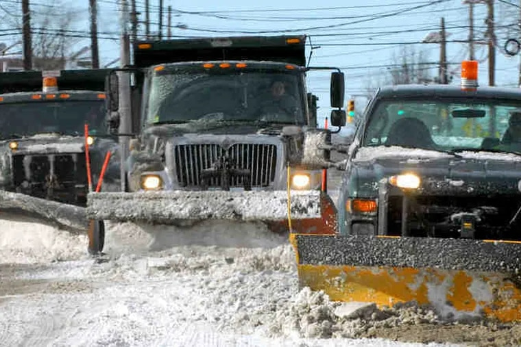 Trucks form a snow-plow train yesterday along Maple Avenue on the border between Pennsauken and Cherry Hill.