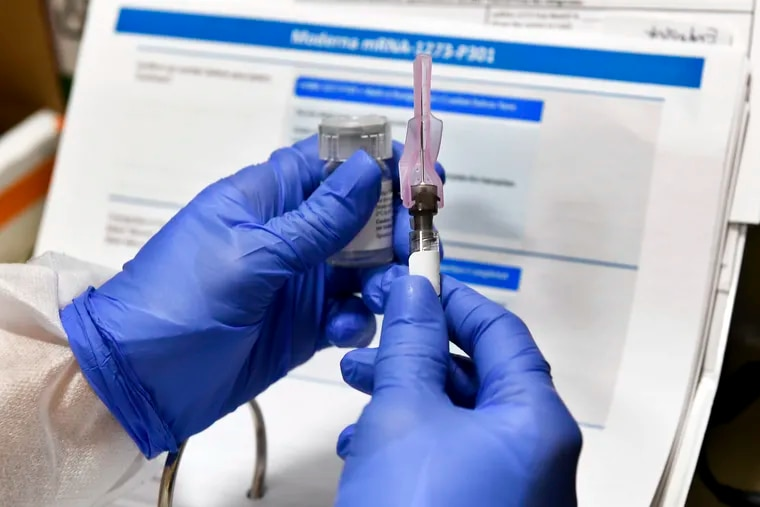 A nurse prepares a shot that is part of a possible COVID-19 vaccine, developed by the National Institutes of Health and Moderna Inc., in Binghamton, N.Y., in July.