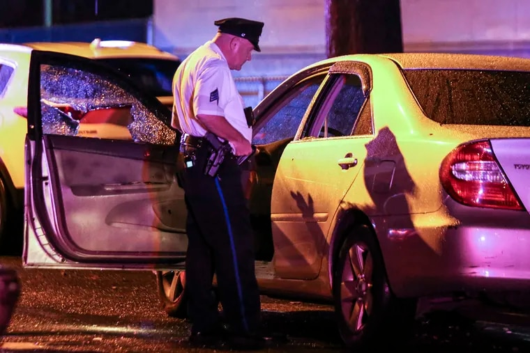 A police sergeant on the 3500 block of North 21st Street looks over a car where a man was shot. He was transported to Temple University Hospital, where he died a short time later. Thursday, Sept. 22, 2021