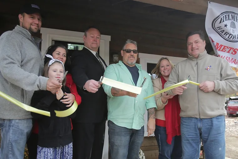 A ribbon-cutting ceremony in held in front of a refurbished cabin. From left, Pastor, Donnie Davis from Amazing Grace ministry: his daughter Sophia Davis, 10; his wife Jennifer Davis; Bryan Bush from Sheet Metal Workers Local Union 19; Anthony Raymond -- Director of Operation Safe Haven; Tammy Koller and her husband Ron Koller who is from Sheet Metal Workers Local Union 19.