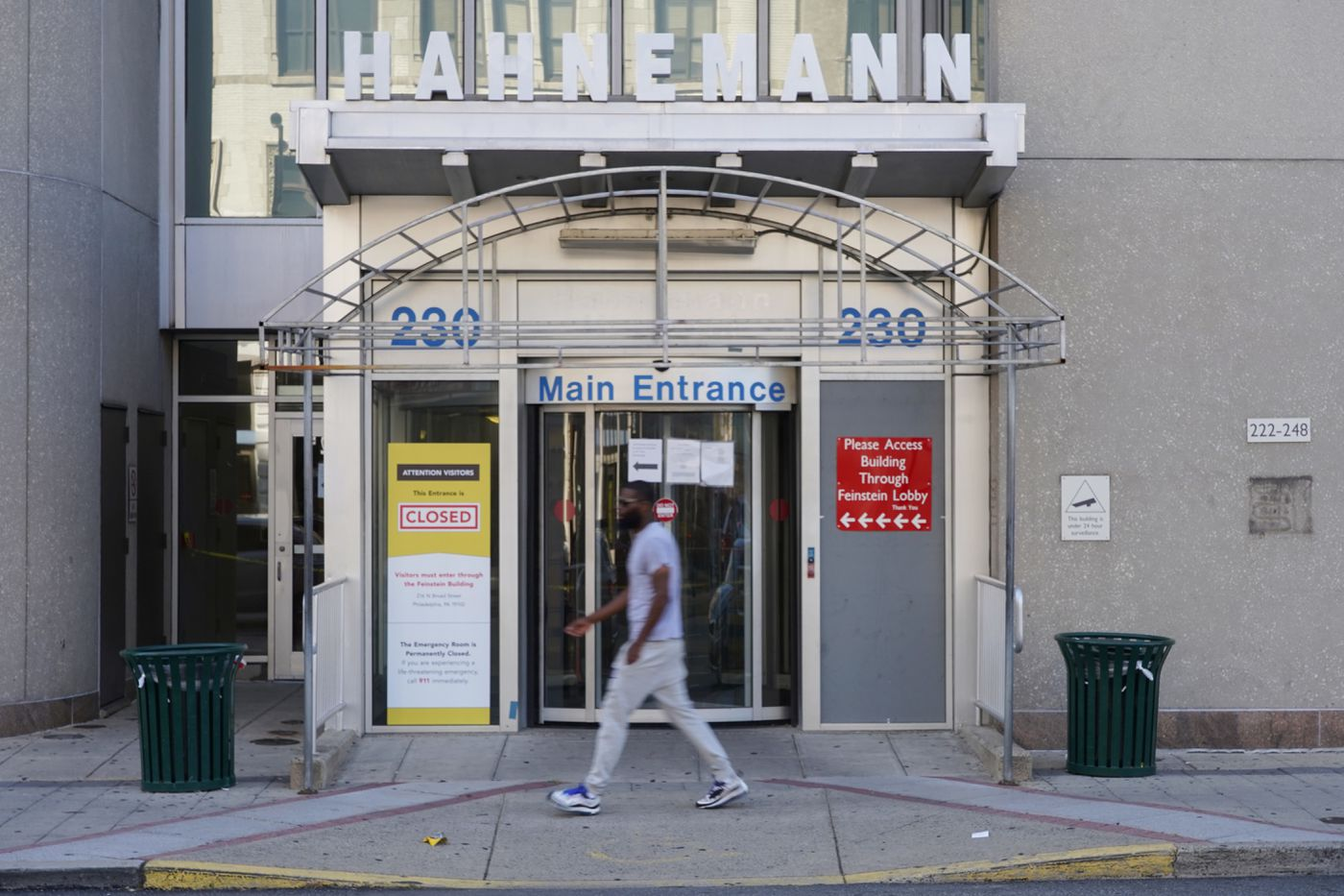 A pedestrian walks by the the closed sign on the main entrance of Hahnemann University Hospital in August.