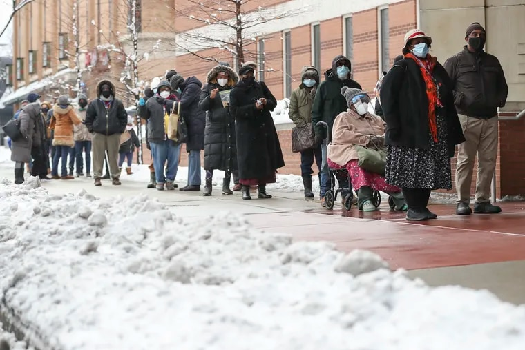A long line of people wait outside to receive their COVID-19 vaccine as snow falls outside the Liacouras Center in Philadelphia on Feb. 2, 2021. The pandemic has made people more aware of the importance of having health insurance, and many are getting covered under Medicaid.