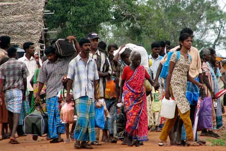 Ethnic Tamils leave camps for displaced persons in Manik Farm, Sri Lanka. After the war ended, the government herded civilians into the camps, which are to be closed by the end of January.