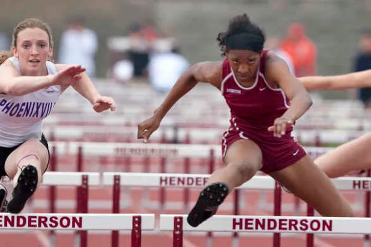 Abington's Leah Nugent (right) beats out Phoenixville's Lauren Terstappen in the 100-meter hurdles at the Henderson Track and Field Classic at West Chester Henderson.