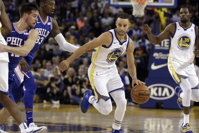 Golden State's Stephen Curry, center, drives the ball away from T.J. McConnell, left, and Robert Covington (33).