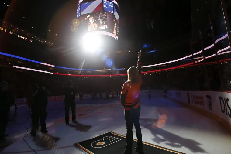 Lauren Hart raising her arm after singing the national anthem last year at a Flyers home game against the New York Rangers.