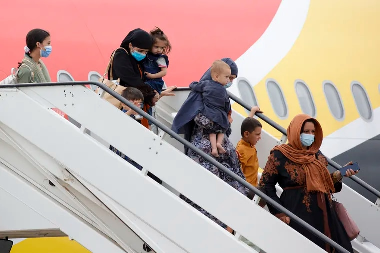 People disembark from a Belgian chartered plane, as part of an evacuation from Afghanistan, upon arrival at Melsbroek Military Airport in Melsbroek, Belgium, Thursday, Aug. 26, 2021.