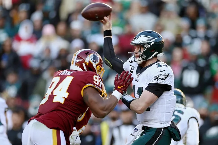 Eagles quarterback Carson Wentz throws a pass under pressure from Washington Redskins defensive lineman Daron Payne during the third quarter. Payne ended up hitting Wentz and getting flagged for roughing the passer.