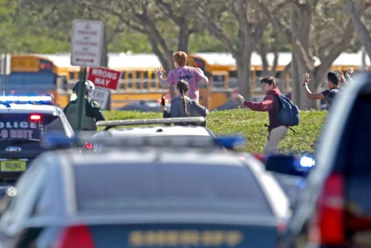 Students run wth their hands in the air outside of Stoneman Douglas High School in Parkland, Fla. after reports of an active shooter on Wednesday, Feb. 14, 2018.