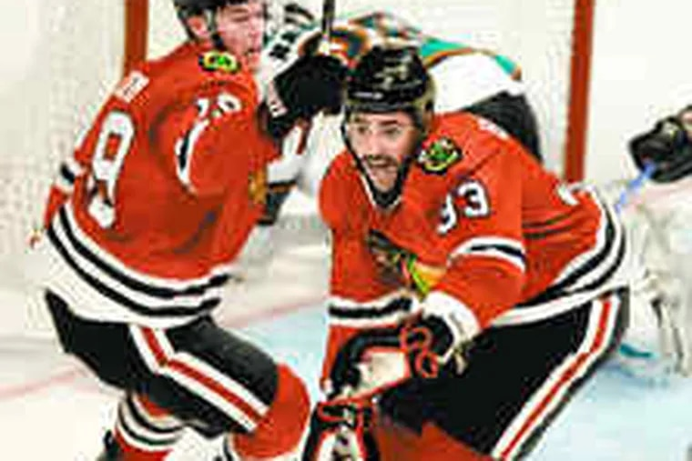 """Dustin Byfuglien (33) celebrates his clinching Game 4 goal against the San Jose Sharks with teammate Jonathan Toews. """"Big Buff"""" is likely to be challenged in front of the net by Flyers defenseman Chris Pronger, right, tangling with Montreal's Scott Gomez."""