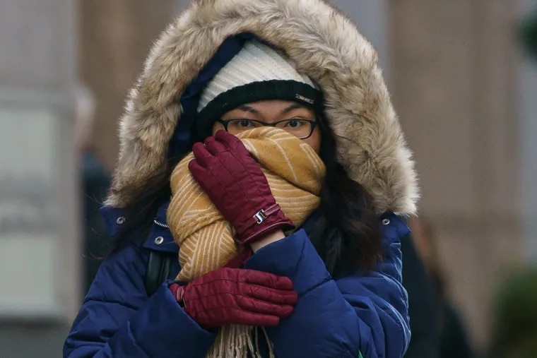 Tam Huynh bundles up against the cold at 18th and Market Streets last month. After a flirtation with April-like weather on Tuesday, Wednesday will be a coat situation.