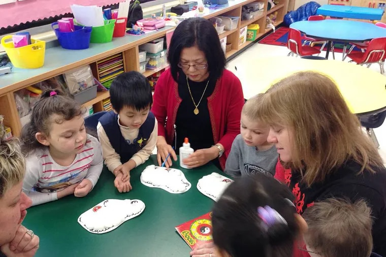 In this Feb. 19, 2015 photo, from left, Skyler Demars, Kevin Hu, Mandarin teacher Shwu-Ching Wang, Hunter Hatch and kindergarten teacher Lisa Halloran decorate sheep in honor of the Lunar New Year at the Mohegan Elementary School in Montville, Conn. At Connecticut's casinos, the staff can speak to you in nearly any Asian language. The diversity of the workforce at the casinos, which cater heavily to Asian gamblers from New York, is changing the complexion of nearby public schools that have been hiring more language specialists and adding new cultural traditions. (AP Photo/Michael Melia)