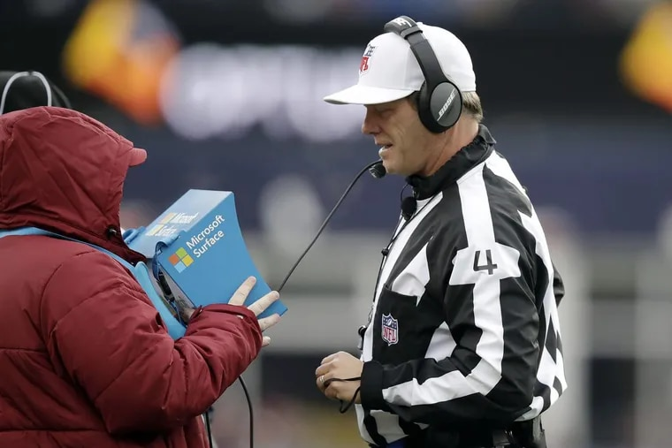 Referee Craig Wrolstad reviews a video replay on the sideline during the second half of an NFL football game between the New England Patriots and the Buffalo Bills, Sunday, Dec. 24, 2017, in Foxborough, Mass.