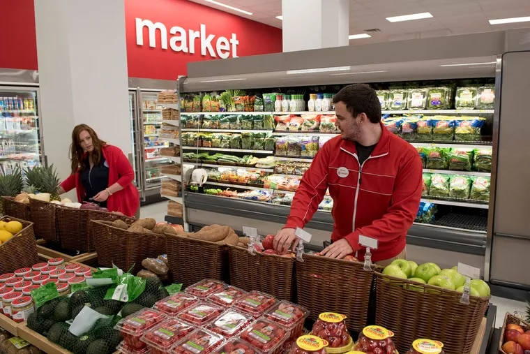 Arielle Schwarz (left), store team leader, and Marcus Farley, senior team leader, arrange produce at the new Target on Chestnut Street near 11thin Philadelphia on July 19, 2016.