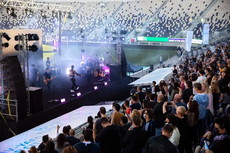 """Israeli musician Ivri Lider performs in front of an audience at a soccer stadium in Tel Aviv where all guests were required to show """"green passport"""" proof of receiving a COVID-19 vaccination or full recovery from the virus."""