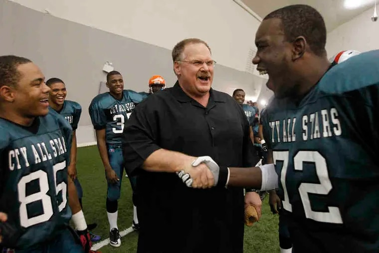 Eagles coach Andy Reid shakes hands with Dajuan Franks, a lineman from Frankford.
