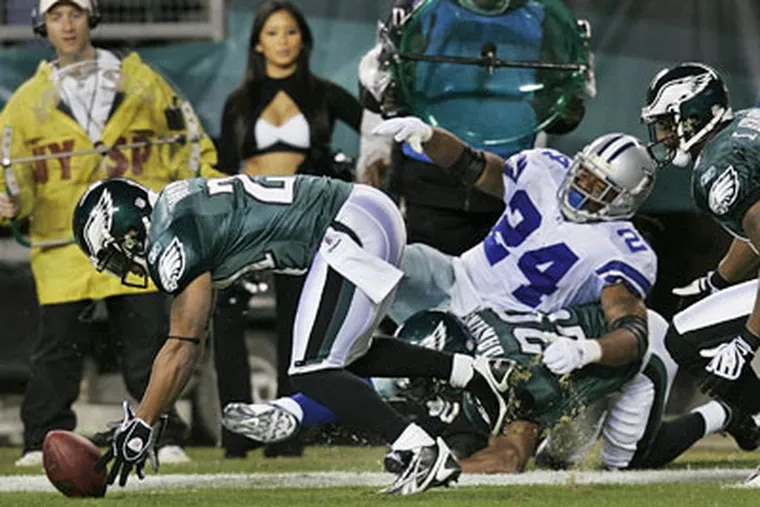 Cowboys running back Marion Barber fumbles the ball as he is hit by Eagles Brian Dawkins and Joselio Hanson recovers during the third quarter of Sunday's game. Hanson ran the ball back for a touchdown and the Eagles routed the Cowboys, 44-6. (AP Photo / Mel Evans)
