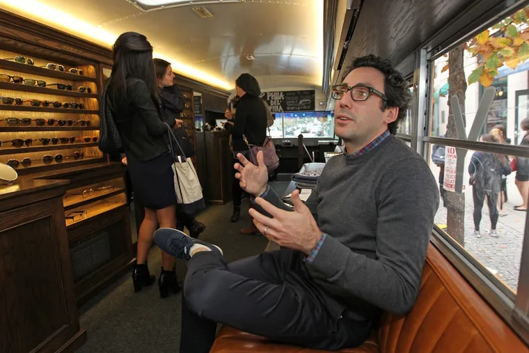 """Neil Blumenthal, one of the co-founders of Warby Parker, talks about his business vision aboard the tour bus. The brand, which was founded by four Wharton students, is """"trying to radically transform the optical industry,"""" said Blumenthal. ( MICHAEL BRYANT / Staff Photographer )"""