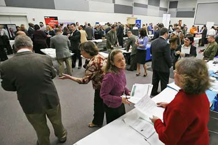 Former Circuit City paralegal Betsy Wade, center, hands her resume to recruiter Linda George, right, during a job fair at the headquarters of Circuit City in Richmond, Va. The government said Thursday that new claims for unemployment benefits jumped to their highest level in more than 26 years. (AP Photo/Steve Helber)