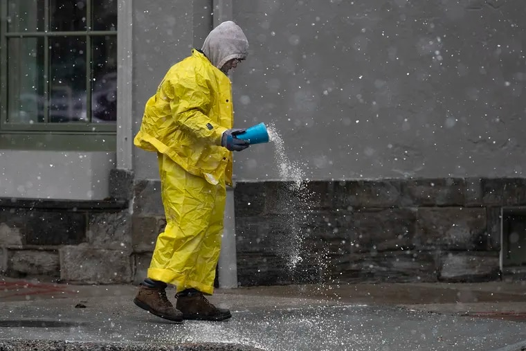 A worker throws salt onto the curb off of Germantown Avenue as a light snow fell in Chestnut Hill early on Dec. 2.