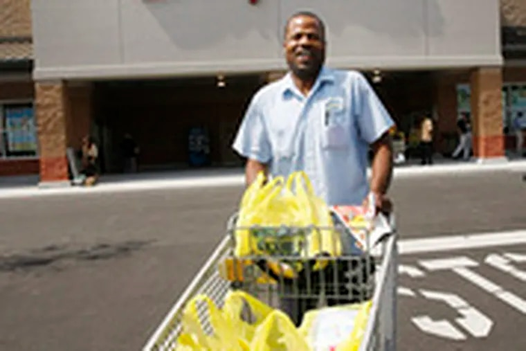 Dennis Carty wheels his purchases out of the new ShopRite at 52nd and Jefferson streets in West Philadelphia yesterday. One neighbor said it's been 20 years since the area had a grocery store.